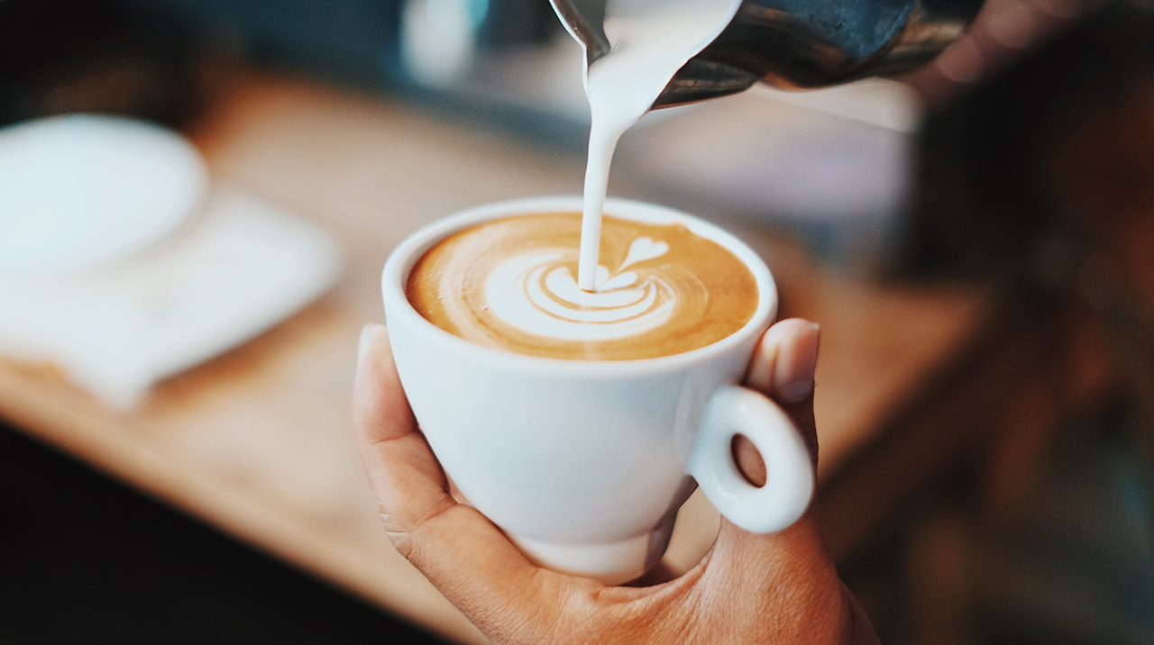 frothed milk being poured into cappuccino in white cup